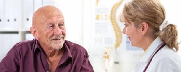 Oudere man krijgt informatie van een vrouwelijke arts in een ziekenhuisomgeving