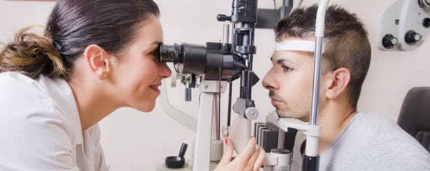 Arts kijkt in de lens van een oogmeetapparaat om de ogen van een jonge man te meten, die aan de andere kant van het apparaat zit.