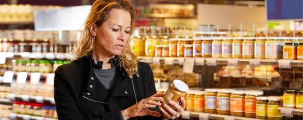 Vrouw in supermarkt checkt etiket op suiker