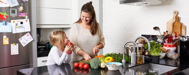 Vrouw in keuken vervangt suikerrijke voeding door gezonde groenten