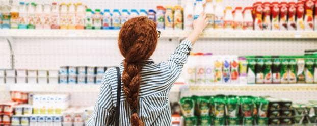 Vrouw pakt zuiveldrank in supermarkt