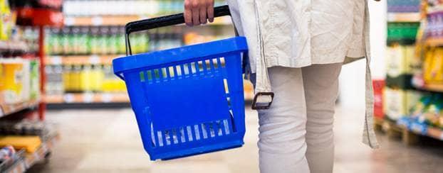 Vrouw in de supermarkt checkt producten op suiker en calorieën