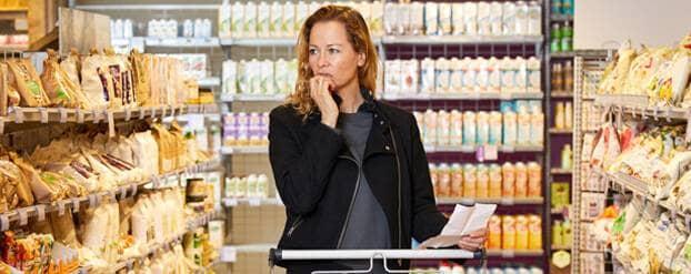 Vrouw in de supermarkt vraagt zich af hoe ze suikervrij moet eten