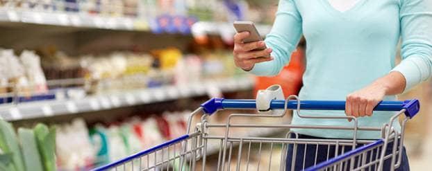 Vrouw zoekt naar suikervrije producten in de supermarkt