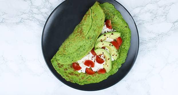 Foto spinaziepannenkoeken belegd met hüttenkäse en avocadosalade
