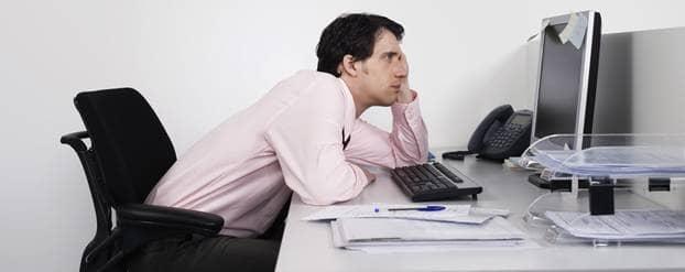 Man hangt voor de computer aan bureau