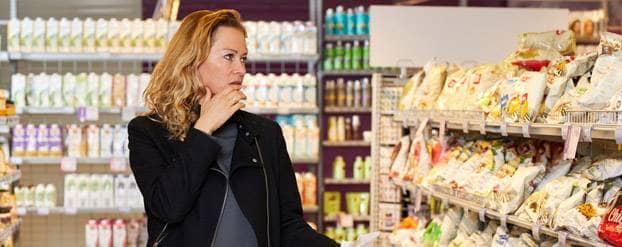 Vrouw probeert verleidingen te weerstaan in de supermarkt
