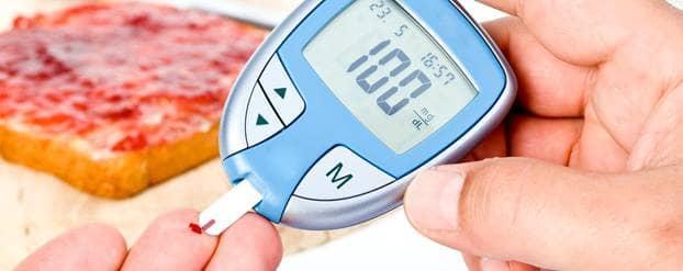 Een hand waarbij één van de vingers een druppel bloed heeft, terwijl de andere hand een glucosemeter vasthoudt die de bloedsuikerwaarde meet.