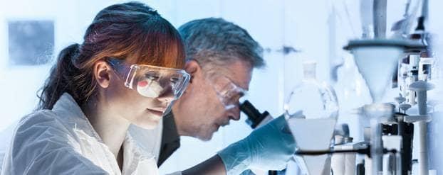 Onderzoekers met reageerbuizen en microscopen