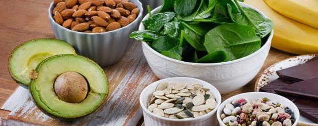 Een compositiefoto van bananen, pure chocolade, avocado, opgesteld met schaaltjes vol gezonde voeding: spinazie, amandelen, pitten, zaden en yoghurt